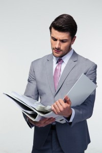 Handsome businessman reading documents over gray background